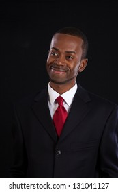 Handsome black businessman in suit and red tie with a white shirt looking to the left with a confidant smile