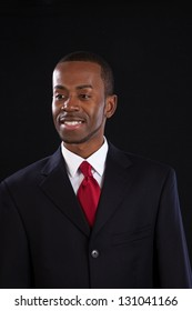 Handsome black businessman in suit and red tie with a white shirt looking left with a confidant smile