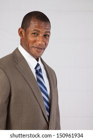 Handsome black businessman  in a suit and tie  and a dress shirt,  looking  at the camera with a pleased smile