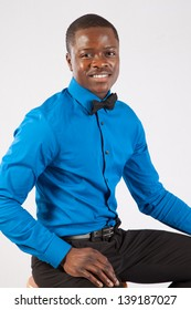 Handsome black man in bow tie and blue shirt, sitting on a wooden stool and  looking at the camera with a happy expression