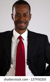 Handsome black man in a business suit, standing and looking assured as he smiles at the camera
