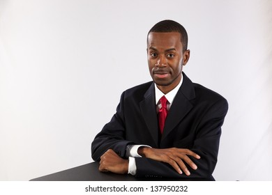 Handsome black man in a business suit, with his arms crossed on the table before him and looking at the camera with a serious look.