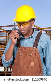 Handsome black man construction worker talking on a walkie talkie