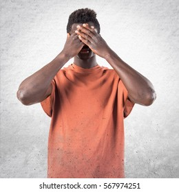 Handsome black man covering his eyes