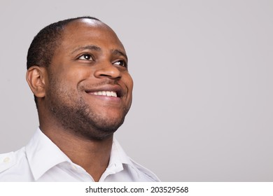handsome black man looks happy. man smiling and looking up on white