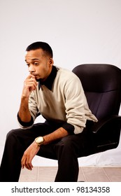 Handsome Black man in an office chair, thinking and considering with chin in hand