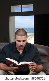 A handsome black man reading a book