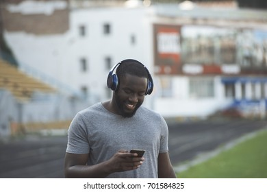 A handsome black man runner is resting by the sports track while using an app in his mobile smart phone to listen to music, wearing headphones