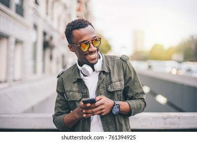 Handsome black man with smartphone and headphones.