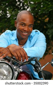 Handsome black man smiling while sitting on a motorcycle.