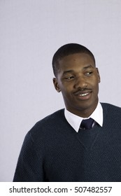 Handsome black man in sweater and tie, smiling with pleasure