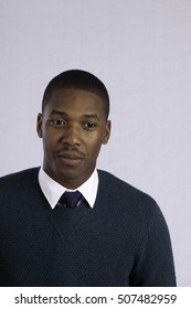 Handsome black man in sweater and tie, looking thoughtful