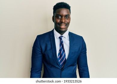 Handsome black man wearing business suit and tie with a happy and cool smile on face. lucky person.