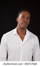 Handsome Black man in a white shirt, looking thoughtful