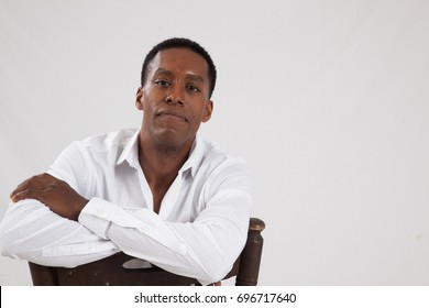 Handsome Black man in a white shirt, sitting backwards on a chair and  looking thoughtful