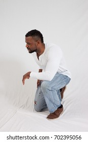 Handsome Black man in white shirt and jeans, with a thoughtful expression kneeling