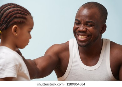 Handsome black young father cheering up his tired cute little daughter against pale blue background. Smiling for her, putting hand on her shoulder