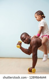 Handsome black young father is doing push ups on dumbbells with his cute little daughter riding him. Indoors. He is seriously looking at camera tensing biceps.