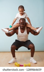 Handsome black young father is doing squats with his cute little daughter riding him. He is having trouble with additional weight, which is funny to her.