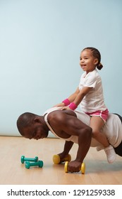 Handsome black young father is doing push ups on dumbbells with his cute little daughter riding him. They both enjoy it big time. Indoors.