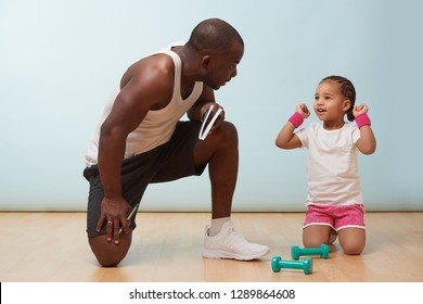 Handsome black young father fitness training his cute little daughter against pale blue background. She happily throws her hands in air victoriously while he commends her performance.