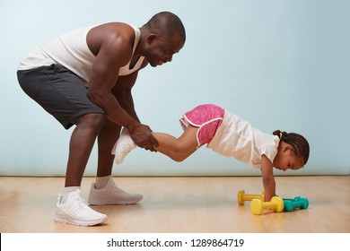 Handsome black young father is helping his cute little daughter to exercise at home. He is holding her legs so she would try advanced elevated push ups.