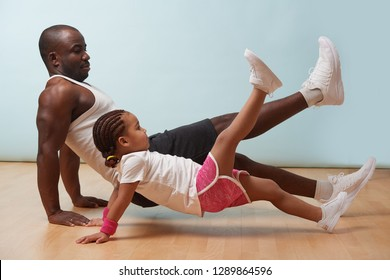Handsome black young father and his cute little daughter are doing reverce plank with leg raise on the floor at home. Family fitness workout.