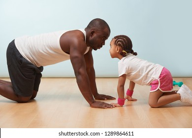 Handsome black young father and his cute little daughter are standing on all fours, stretching together on the floor at home. They are looking at each other face to face.