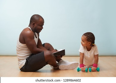 Handsome black young father instructing his cute little daughter on how to exercise with dumbbells, making notes. Against pale blue background. Push ups. She pays close attention.