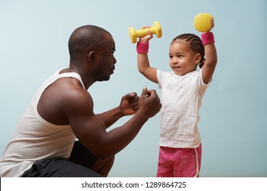 Handsome black young father instructing his cute little daughter on how to exercise with dumbbells against pale blue background. Lifting dumbbells overhead. She smiles and looks at him for approval.