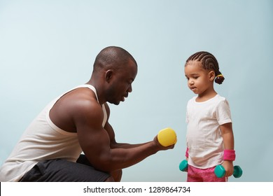 Handsome black young father instructing his cute little daughter on how to exercise with dumbbells against pale blue background. Biceps curls. She pays close attention.