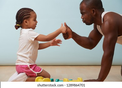 Handsome black young father is thumb wrestling with his cute little daughter on the floor at home. They looking at each other, trying to show their resolve.