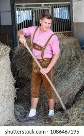handsome blond bavarian man with pitchfork and hay