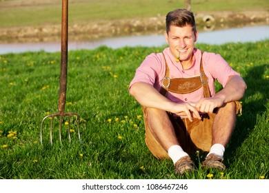 handsome blond bavarian man sitting in the grass