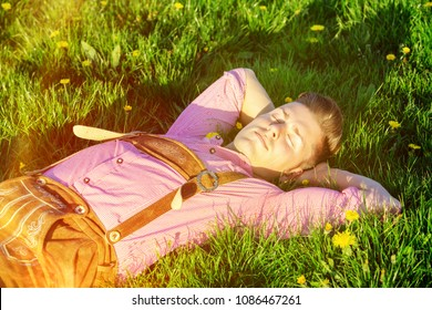 handsome blond bavarian man sleeping in the grass
