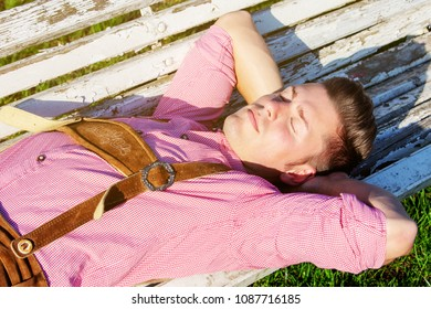 handsome blond bavarian man sleeping outdoors on a bench