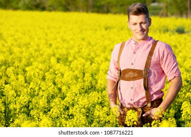 handsome blond bavarian man standing in a field of yellow flowers