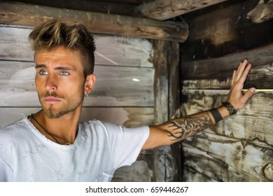 Handsome blond, blue eyed young man leaning against wood planks wall outdoor and looking away to a side