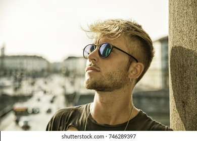 Handsome blond, blue eyed young man leaning against stone wall outdoor and looking to a side in Turin, Italy