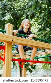 handsome blond boy joyfully plays in the playground on a sunny summer day