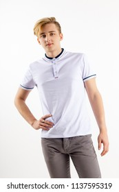 Handsome blond boy teenager in white shirt stands in white studio