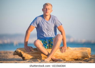 Handsome blond guy sitting on timber on the background of a sea beach
