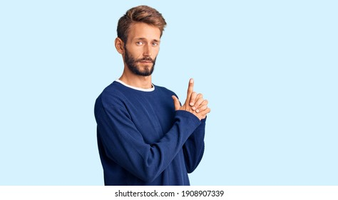 Handsome blond man with beard wearing casual sweater holding symbolic gun with hand gesture, playing killing shooting weapons, angry face