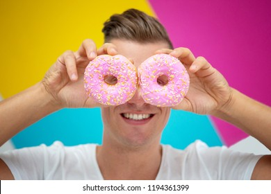 handsome blond man holding two pink donuts in front of colorful background
