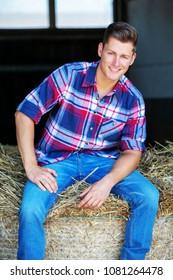 handsome blond man in jeans sitting on haystack