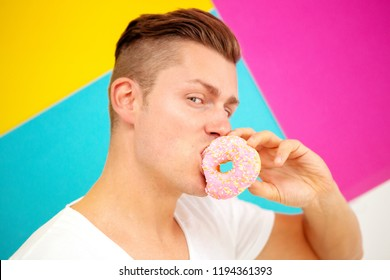 handsome blond man on colorful background eating a pink donut