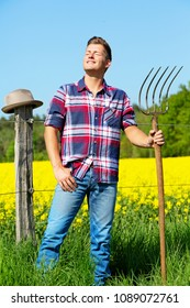 handsome blond man with pitchfork in front of yellow field enjoying the sun