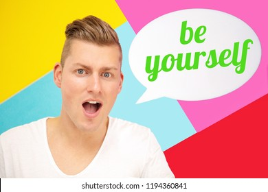 handsome blond man shouting and holding speech bubble with the words Be Yourself