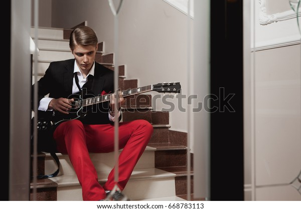 Handsome blond man in a suit playing on an electric guitar sitting on a staircase