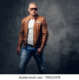Handsome blond, muscular male in sunglasses, dressed in a white t shirt and brown leather jacket.